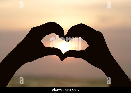 Silhouette a mano a forma di cuore con sunrise nel medio e la spiaggia .come sfondo il concetto di San Valentino con spazi di copia per il tuo testo o disegno. Foto Stock