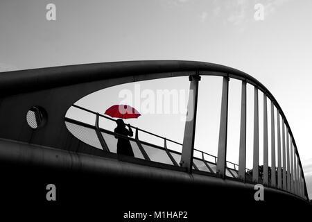 Un'immagine artificiale di una donna in piedi su un ponte con un ombrello rosso durante la giornata di pioggia. Foto Stock