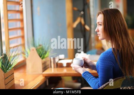 Giovane ragazza in cafe si siede e bevande di tè Foto Stock