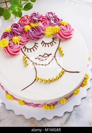 Festosa torta con crema di fiori e una ragazza faccia su uno sfondo luminoso Foto Stock