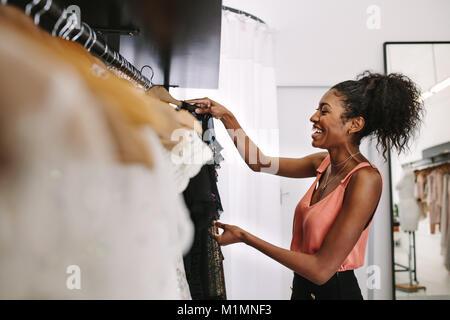 2051b9d210f7 Abito sorridente designer nel suo negozio di stoffa con abiti firmati sul  display. Il cliente