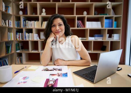 Di mezza età creativo femminile utilizzando computer che sorride alla telecamera Foto Stock