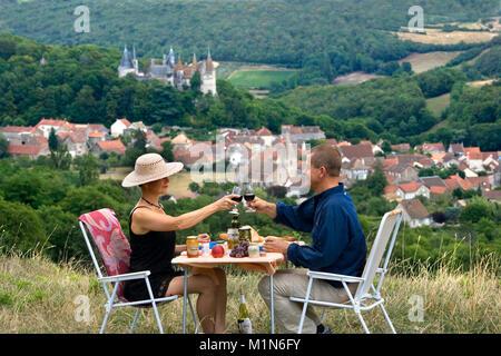 La Francia. La Borgogna. La Rochepot vicino a Beaune. Regione viticola. Coppia avente un picnic con il castello Foto Stock