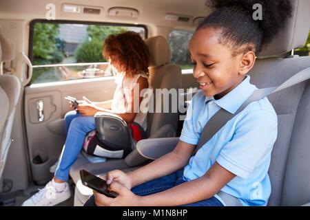 I bambini utilizzando dispositivi digitali sul viaggio In automobile Foto Stock
