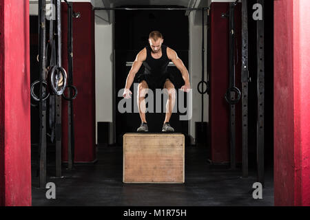 Atleta giovane uomo che fa un salto di scatola di esercizio in palestra Foto Stock