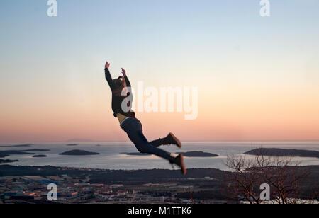 Ragazza saltando su una collina con una vista della città e del mare Foto Stock