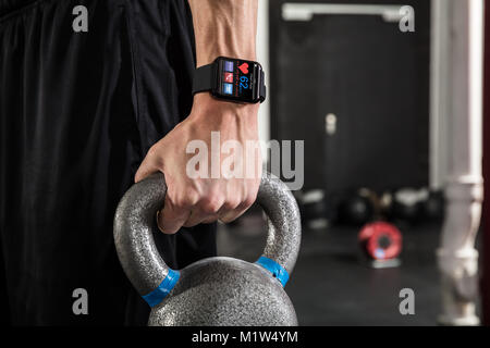 Close-up di un atleta giovane uomo che indossa Smart Watch Holding bollitore campana in palestra Foto Stock