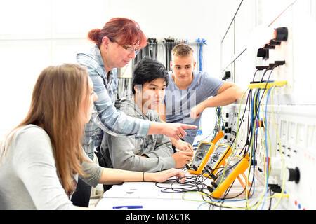 Un gruppo di giovani in tecniche di formazione professionale con l'insegnante Foto Stock