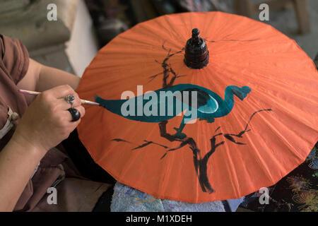 Un Thai craftswoman rendendo tradizionale ombrellone a ombrello facendo centro in Bo Sang centro artigianale su Foto Stock