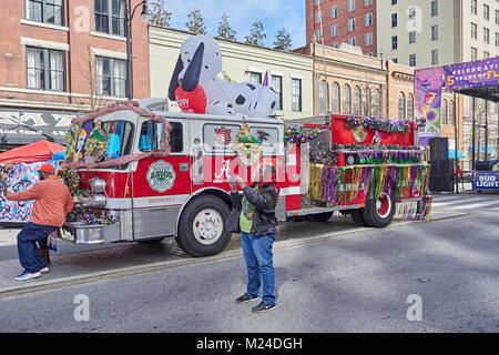 Due persone di scattare le foto e uno un selfie, presso il locale Mardi Gras celebrazione con un decorato camion dei pompieri in background in Montgomelry Alabama, Stati Uniti d'America.