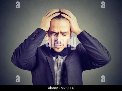 Giovane imprenditore nel soddisfare tenendo le mani sulla testa alla ricerca disperata. Foto Stock