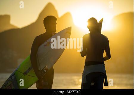 RIO DE JANEIRO - MARZO 20, 2017: Tramonto sagome di due giovani surfisti con tavole da surf a Arpoador con due fratelli montagne sullo sfondo