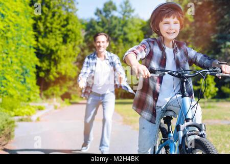 Memori padre figlio di insegnamento caldo a guidare la bicicletta Foto Stock