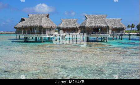 Tropical bungalows con tetto di paglia sul mare nella laguna, Tikehau Atoll, Tuamotus, Polinesia francese, oceano pacifico, Oceania