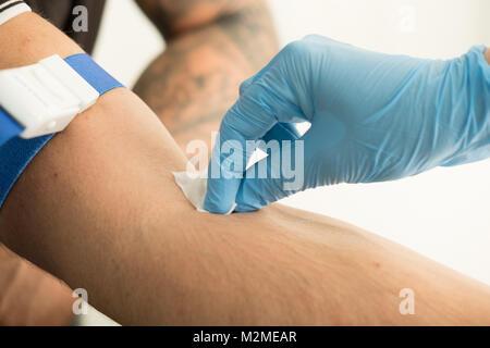 Chiudere l'infermiera puntura per applicazione di lana di cotone con antisettico sul braccio del paziente dopo il Foto Stock