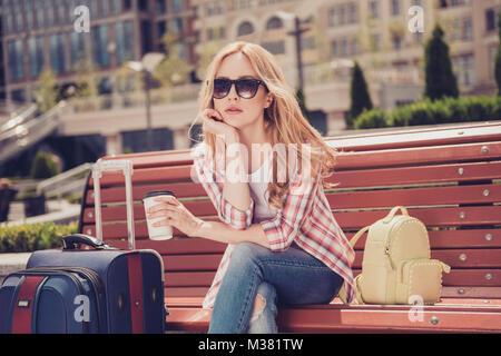 Taxi transtort ricerca doganale concetto all'estero. Sconvolto annoiato infelice bella donna con lunghi biondi capelli Foto Stock