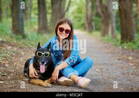 Ragazza giovane con un cane in occhiali da sole nel parco. Pastore Tedesco Foto Stock