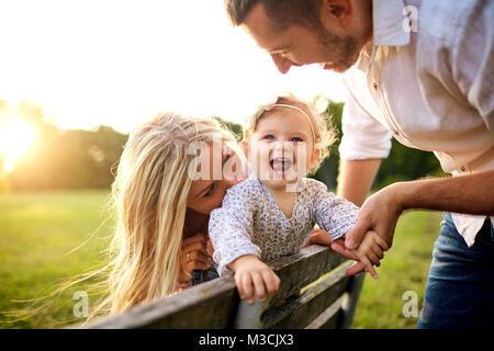 La famiglia felice in un parco in estate autunno. Foto Stock