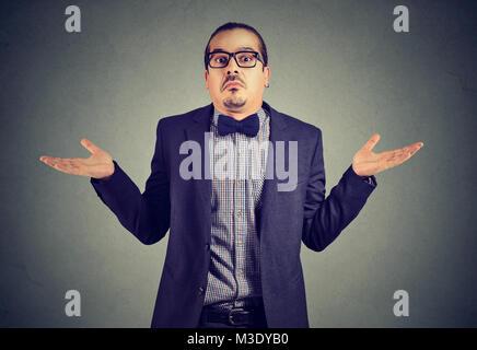 Giovane uomo in abbigliamento formale scrollare le spalle mentre posa sul grigio e cercando confuso. Foto Stock