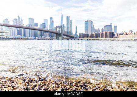 Rocky spiaggia ghiaiosa shore acqua in East River con vista di NYC New York City cityscape skyline e bridge, nessuno Foto Stock
