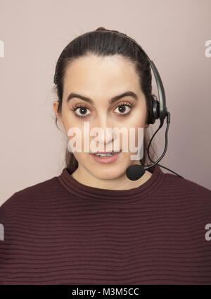 Operatore di call center con un espressione di sorpresa ascoltando una conversazione sul suo auricolare e staring Foto Stock