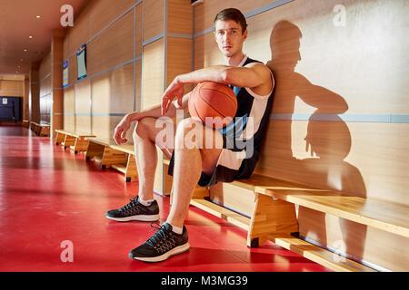 Grave fiducioso giovane giocatore con la palla sulla corte di formazione Foto Stock