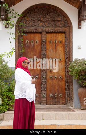 Zanzibar residente nella parte anteriore del tradizionale porta scolpito in pietra città. Foto Stock