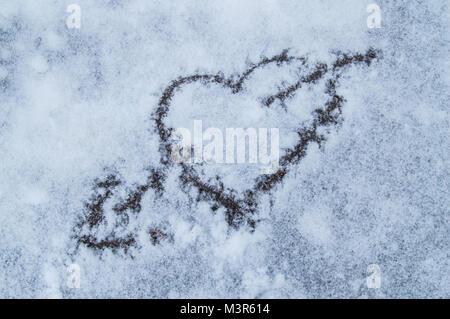 Il giorno di San Valentino. Cuore trafitto da una freccia disegnata sulla neve. Foto Stock