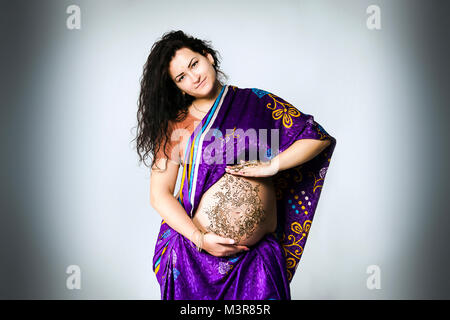Studio ritratto di una donna in stato di gravidanza in Indian sari, una gravidanza pancia dipinta con henné Foto Stock