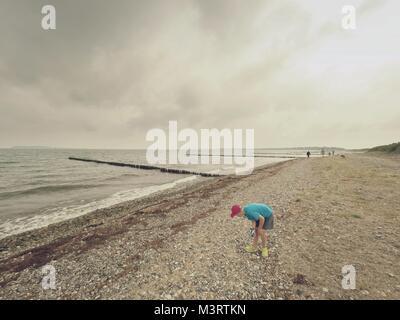 Ragazzo biondo sulla spiaggia alla ricerca di conchiglie. Lungo la spiaggia sassosa con legno frangiflutti per proteggere Foto Stock