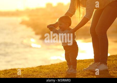 Vista laterale di un bambino ad imparare a camminare e madre aiutandolo sull'erba all'aperto al tramonto con una città in background