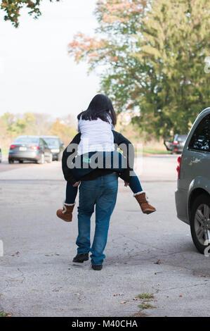 Fratello di dare la sua sorella un piggyback Ride Foto Stock