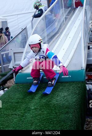 """Un giovane ragazzo prende il largo sul """"baby ski jumping hill' per bambini. Ljubno ob Savinji, Slovenia. Foto Stock"""
