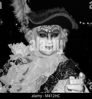 Maschio goer di carnevale in costume tradizionale e la maschera in piedi con la schiena al Canal Grande e gondole Foto Stock