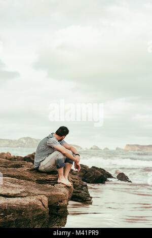 Giovane uomo godendo la giornata in spiaggia Foto Stock