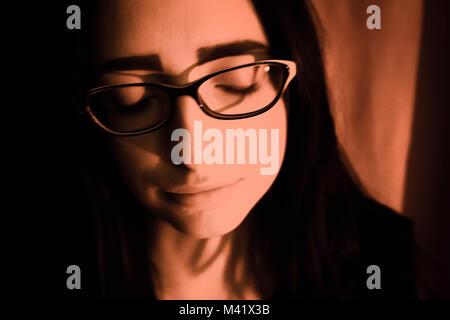 Ritratto di una ragazza con una luce arancione su di lei. Foto Stock