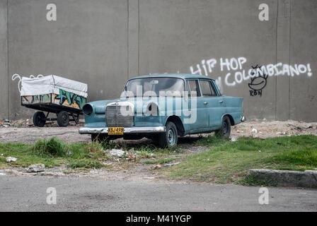 Una scena di strada di una macchina vecchia, un carrello di riciclaggio e una parete con graffiti in spagnolo Foto Stock