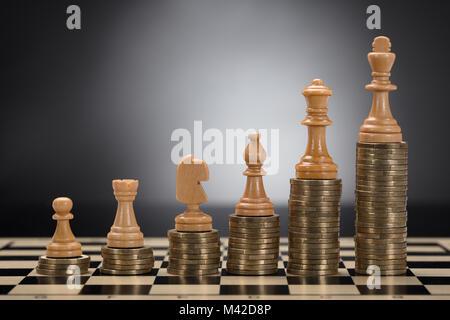 Close-up di scacchi Pezzi impilati monete d oro contro lo sfondo grigio Foto Stock