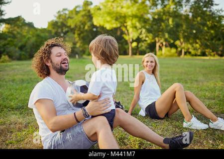 La famiglia gioca con una palla nel parco. Foto Stock