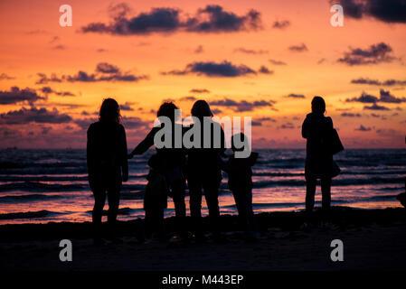 Golden, colorato, abstract Mare vista tramonto all orizzonte con persone sagome vibrante paesaggio di cielo e onde Foto Stock