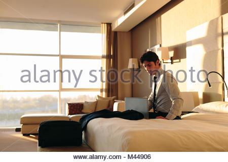 Uomo d affari con computer portatile sul letto di hotel bedroom Foto Stock