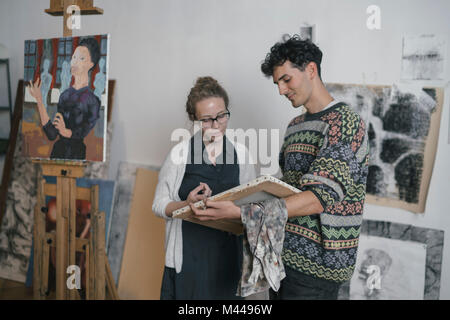 Artista maschio e femmina client guardando in canvas artists studio Foto Stock