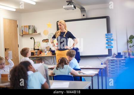 Insegnante con le mani sui fianchi nella parte anteriore della classe presso la scuola primaria Foto Stock