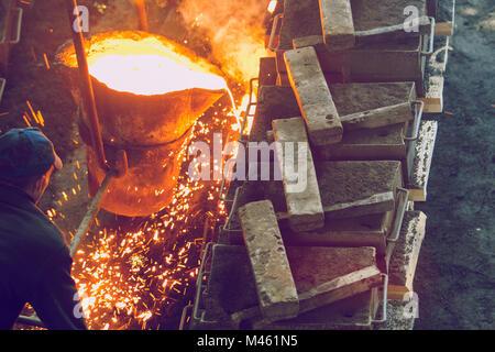 Cesis, Lettonia, fonderia, lavoratori pour metallo, fabbrica in città Cesis 2011. Foto Stock