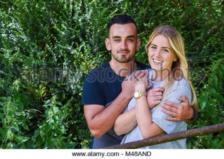 Abbracci uomo sorridente ragazza bionda dietro il punto di iniezione Foto Stock