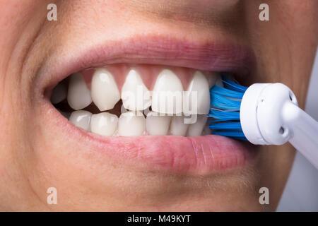 Close-up di una donna di denti con spazzolino da denti elettrico Foto Stock