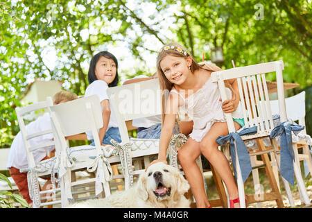 Ragazza accarezzando un Golden Retriever presso il Garden Party in estate Foto Stock