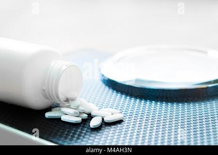 Pillole di perdita di peso su una scala. La dieta medicina versato fuori dal flacone. Foto Stock