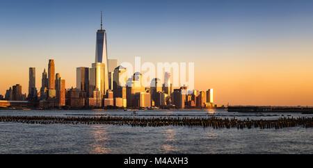 New York City Financial District skyline (Lower Manhattan) al tramonto attraverso il Fiume Hudson Foto Stock