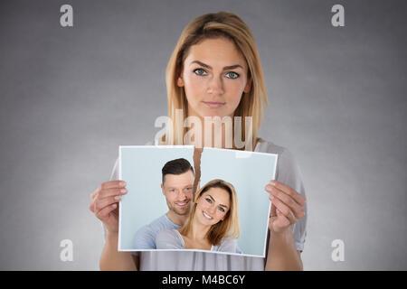 Ritratto di una giovane donna azienda fotografica strappata contro uno sfondo grigio Foto Stock